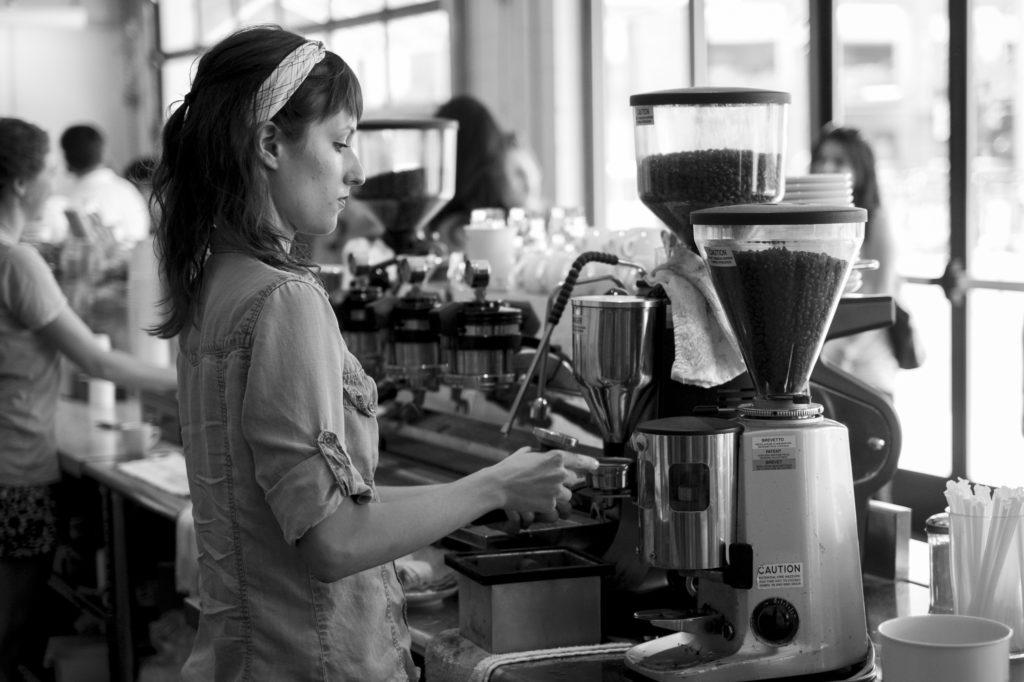 Jauna moteris kavinėje ruošia kavą.