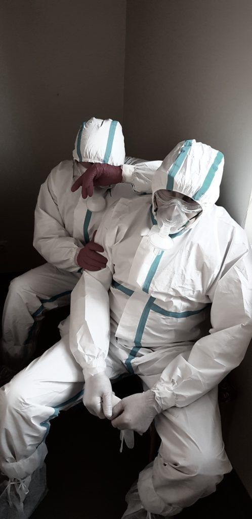 Nuotraukoje pavaizduoti du sėdintys pavargę sveikatos apsaugos darbuotojai, apsivilkę apsauginius kostiumus ir kaukes.