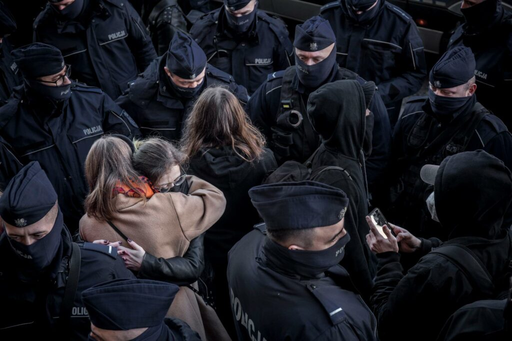 Dvi moterys apsikabinusios viena kitą policininkų apsuptyje.