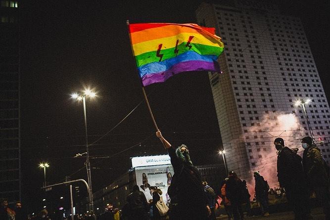 Žmogus protestuojančioje minioje laiko iškeltą LGBT+ vėliavą su trimis raudonais žaibais.