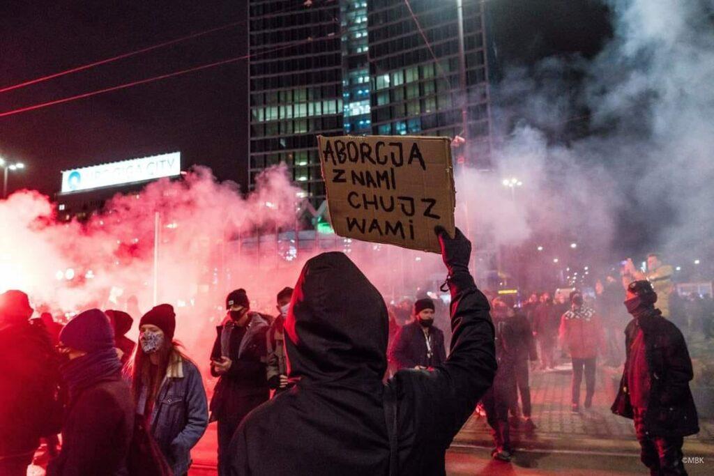 """Protesto dalyvis laiko savadarbį plakatą su užrašu """"aborcja z nami chuj z wami""""."""