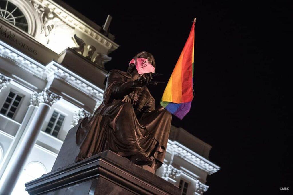 Koperniko skulptūra, kuriai įteikta LGBT+ vėliava, o ant veido užrišta rausva skara su anarcho-trans ženklu.