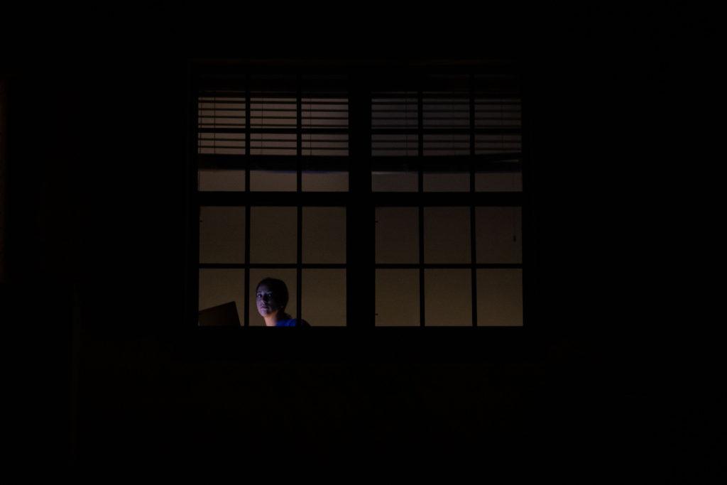 Tamsiame fone – namo langas, per kurį matyti prie kompiuterio sėdinti moteris