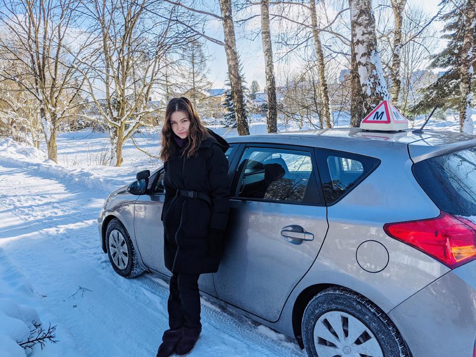 Aldona Juozaitytė stovi prie savo automobilio