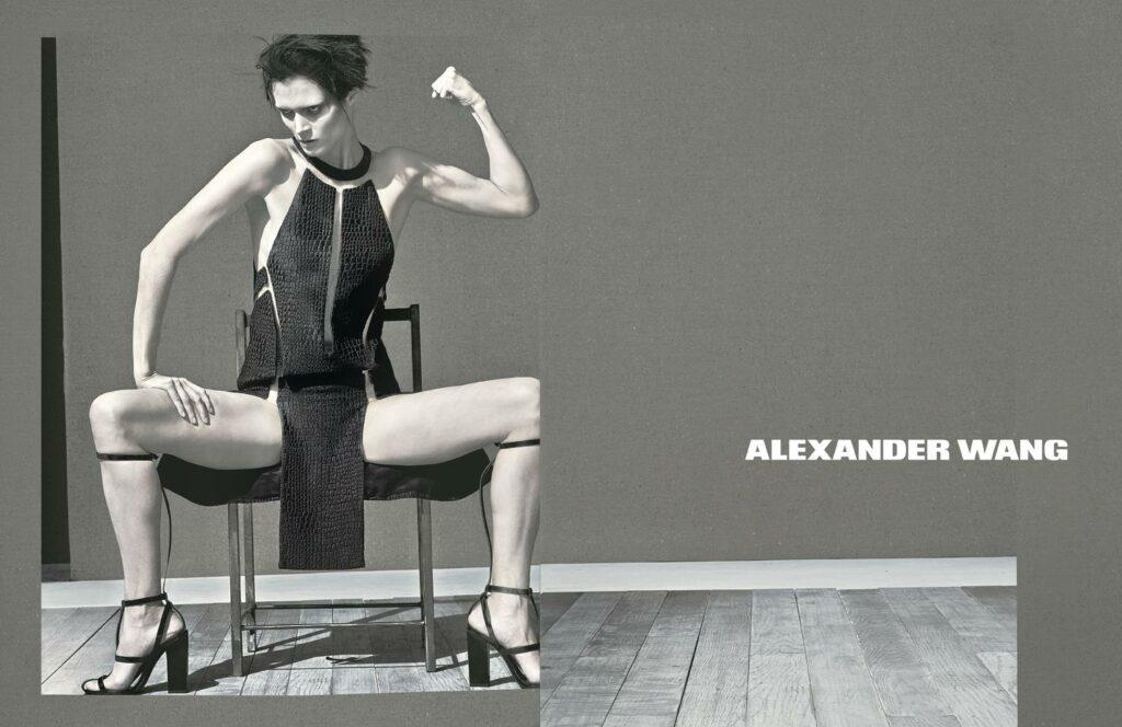 Mados reklama kurioje moteris sėdi ant kėdės iškėlusi kumštį.