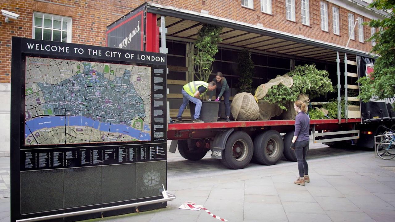 Žmonės iš sunkvežimio iškelia augalus vazonuose, šalia – Londono žemėlapis