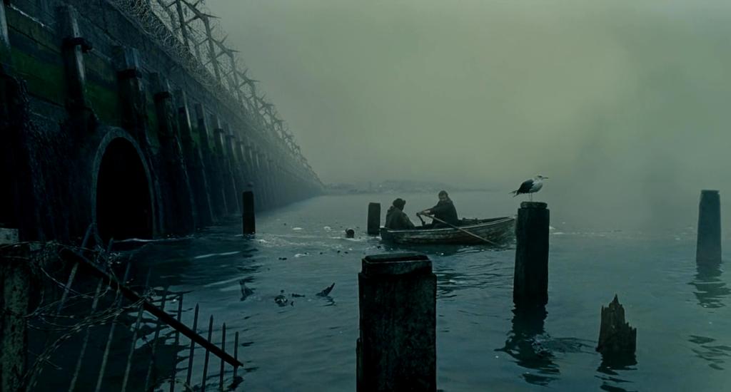 Kadras iš filmo Žmonių vaikai: du žmonės plaukia valtele palei apgriuvusį tiltą