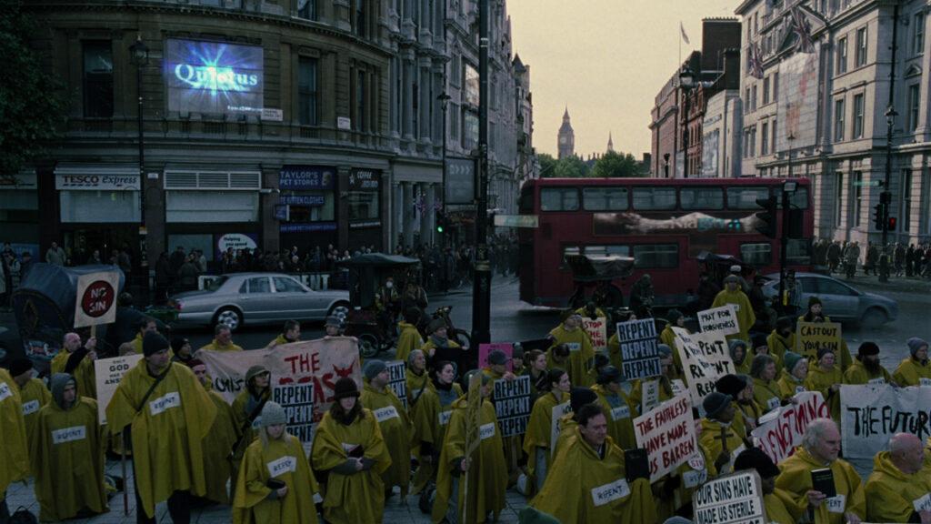 Pilkas distopinis Londonas, kuriame protestuoja geltonais lietpalčiais apsirengę žmonės