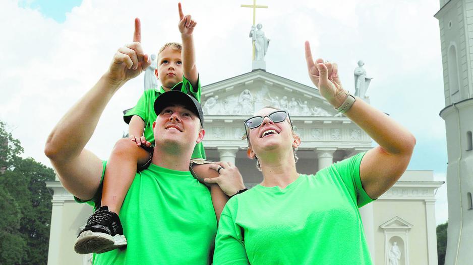 vyras, moteris ir vaikas žaliais marškinėliais rodo į dangų Vilniaus katedros fone