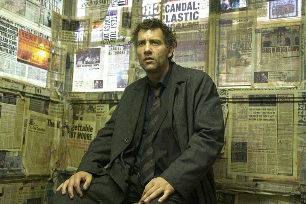 Kadras iš filmo Žmonių vaikai: apšiuręs vyras sėdi prie laikraščiais išklijuotos sienos
