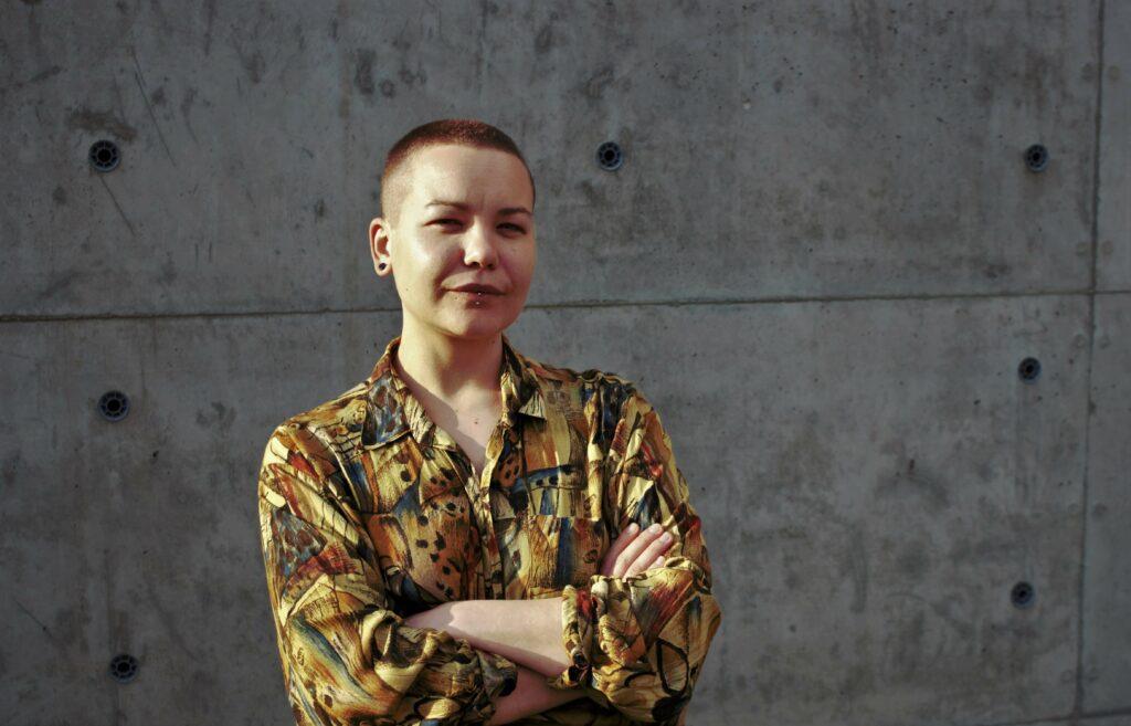 Viktorija Kolbešnikova pilkos mūrinės sienos fone