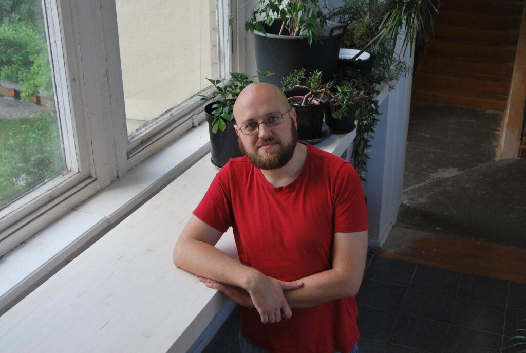 Tomas Marcinkevičius su raudonais marškinėliais, pasirėmęs ant palangės