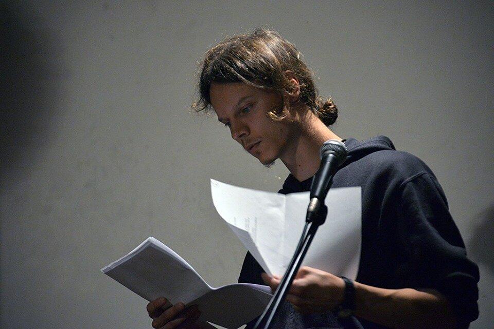 Tadas Zaronskis su popieriaus lapais pilkame fone